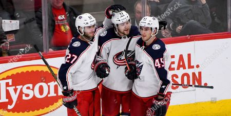 Columbus Blue Jackets right wing Josh Anderson (77) celebrates with defenseman Ryan Murray (27) and center Lukas Sedlak (45) after scoring a goal against the Chicago Blackhawks during the third period of an NHL hockey game, in Chicago