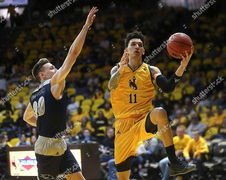 Wyoming forward Trace Young (11) shoots next to Nevada guard David Cunningham (20) during the second half of an NCAA college basketball game, in Laramie, Wyo