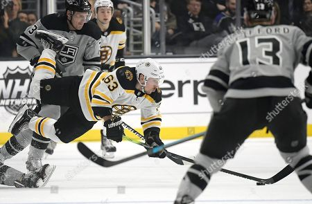 Brad Marchand, Dion Phaneuf, Kyle Clifford. Boston Bruins left wing Brad Marchand, center, trips as he passes the puck while under pressure from Los Angeles Kings defenseman Dion Phaneuf, left, as left wing Kyle Clifford, right, watches during the third period of an NHL hockey game, in Los Angeles. The Bruins won 4-2