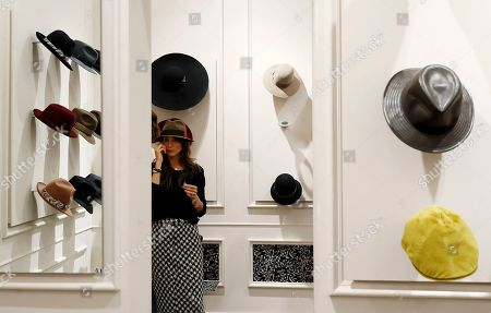 Stock Picture of A woman tries a hat inside a Borsalino hat store in downtown Milan, Italy, . If the traditional Italian hat-maker Borsalino was once synonymous with the fedora, its new private equity owners want to imbue the brand with cachet that extends to couture, sportswear and streetwear for women and Millennials -- without alienating its classic customers and the silhouette that helped shape the rough-and-tumble images of Robert Redford, Frank Sinatra and, perhaps no one more than, Humphrey Bogart