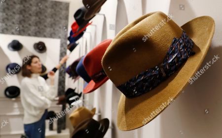 A woman looks at hats in a Borsalino store in downtown Milan, Italy, . If the traditional Italian hat-maker Borsalino was once synonymous with the fedora, its new private equity owners want to imbue the brand with cachet that extends to couture, sportswear and streetwear for women and Millennials -- without alienating its classic customers and the silhouette that helped shape the rough-and-tumble images of Robert Redford, Frank Sinatra and, perhaps no one more than, Humphrey Bogart