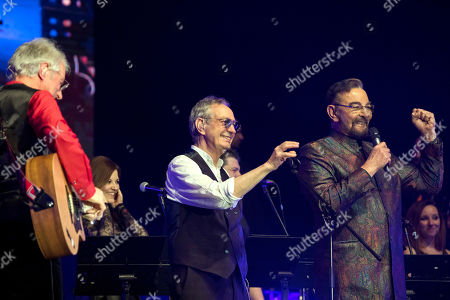 Stock Image of Italian musicians and composers Guido De Angelis (C) and Maurizio De Angelis (L) welcome Italian actor Kabir Bedi (R) on the stage during their concert in Papp Laszlo Sports Arena in Budapest, Hungary, 16 February 2019 (issued on 17 February).