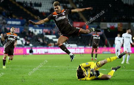Ollie Watkins of Brentford jumps over Kristoffer Nordfeldt of Swansea City.