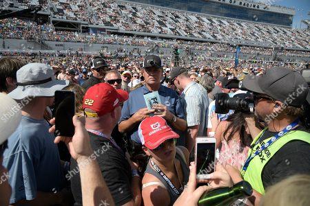 FOX Sports analyst Michael Waltrip, center, walks through the crowd on pit road before the NASCAR Daytona 500 auto race at Daytona International Speedway, in Daytona Beach, Fla