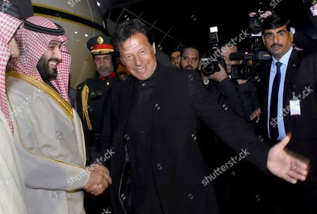 In this photo released by the Press Information Department, Pakistani Prime Minister Imran Khan, centre, greets Saudi Arabia's Crown Prince Mohammed bin Salman, left, upon his arrival at Nur Khan airbase in Rawalpindi, Pakistan, . Saudi Arabia's powerful Crown Prince Mohammed bin Salman began his four-day regional visit on Sunday, arriving in Pakistan where he is widely expected to sign agreements worth billions of dollars to help the Islamic nation overcome its financial crisis