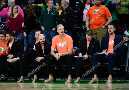 North Dakota Fighting Hawks head coach Brian Jones (center) and his assistants go barefoot and wear Hope shirts supporting the Samaritans Feet charity during a NCAA basketball game between the Oral Roberts University Golden Eagles and the University of North Dakota Fighting Hawks at Betty Engelstad Sioux Center in Grand Forks, ND. UND defeats ORU 85-73