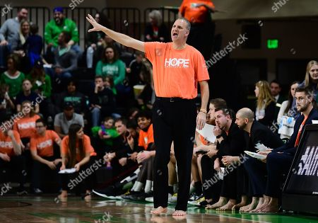 Stock Picture of North Dakota Fighting Hawks head coach Brian Jones directs his team during a NCAA basketball game between the Oral Roberts University Golden Eagles and the University of North Dakota Fighting Hawks at Betty Engelstad Sioux Center in Grand Forks, ND. Jones is barefoot and wearing a HOPE shirt in support of the charity Samaritans Feet. UND defeats ORU 85-73