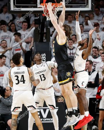 Asbjorn Midtgaard, Trevor Moore, Tre Scott. Wichita State's Asbjorn Midtgaard, center right, dunks against Cincinnati's Trevor Moore (5) and Tre Scott (13) in the first half of an NCAA college basketball game, in Cincinnati