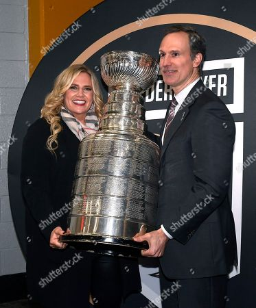 Former Anaheim Ducks defenseman Scott Niedermayer and his wife Lisa pose with the Stanley Cup after his jersey is retired prior an NHL hockey game between the Ducks and the Washington Capitals, in Anaheim, Calif