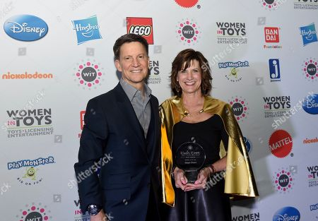 """Stock Picture of Brian Goldner, Gaye Dean. Brian Goldner, Chairman & CEO, Hasbro, presents """"Retailer of the Year"""" award to Gaye Dean, of Target, at the 15th annual Wonder Women Awards, presented by Women in Toys, Licensing and Entertainment (WIT),, in New York"""
