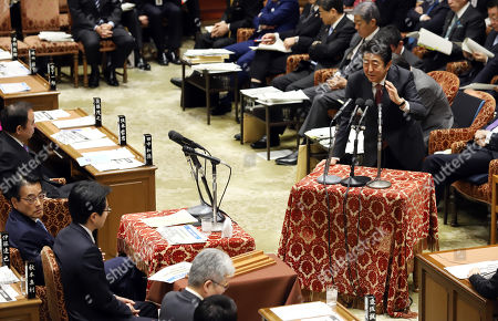 Japanese Prime Minister Shinzo Abe (R) answers a question by an opposition lawmaker Katsuya Okada (L)