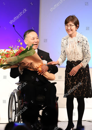 Former Liberal Democratic Party (LDP) president Sadakazu Tanigaki on the wheelchair receives a flower bouquet from former Defense Minister Tomomi Inada