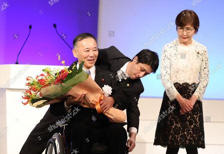 Former Liberal Democratic Party (LDP) president Sadakazu Tanigaki on the wheelchair receives a flower bouquet from former Defense Minister Tomomi Inada