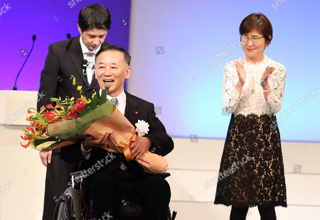 Former Liberal Democratic Party (LDP) president Sadakazu Tanigaki (L) on the wheelchair receives a flower bouquet from former Defense Minister Tomomi Inada