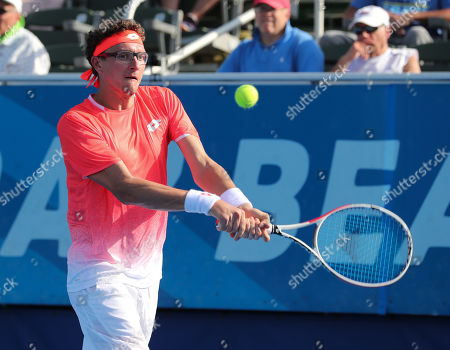 Denis Istomin, of Uzbekistan returns a backhand to Feliciano Lopez, of Spain, during the first round the Delray Beach Open ATP professional tennis tournament, played at the Delray Beach Stadium & Tennis Center in Delray Beach, Florida, USA. Istomin won 7-6(5), 6-2