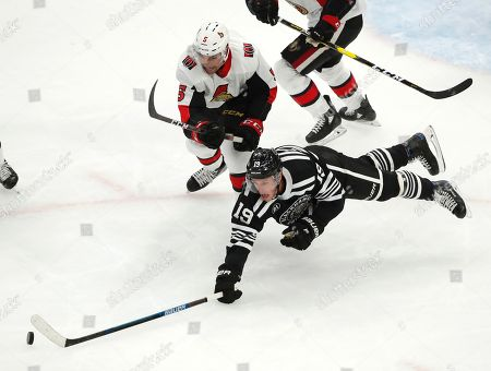 Chicago Blackhawks center Jonathan Toews (19) dives for the puck in front of Ottawa Senators defenseman Cody Ceci (5) during the second period of an NHL hockey game, in Chicago