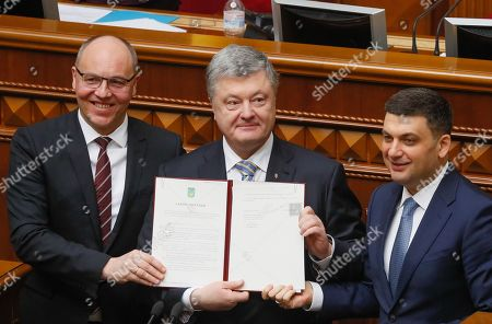 Ukrainian President Petro Poroshenko (C), Prime Minister Volodymyr Groysman (R) and Parliament Speaker Andriy Parubiy (L) hold the just signed law on amending the Constitution on the strategic course of the state to acquire full membership of Ukraine in the EU and NATO, which was voted by Parliament on 07 February 2019, during the extraordinary session of the Ukrainian Parliament in Kiev, Ukraine, 19 February 2019. European Council President Donald Tusk took part in that session of Ukrainian Parliament.