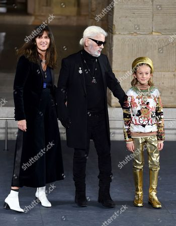 Virginie Viard, Karl Lagerfeld, Hudson Kroenig. Fashion designer Karl Lagerfeld, center, walks with Chanel's fashion creation studio director Virginie Viard and his godson Hudson Kroenig during the finale of the Chanel Metiers d'Art 2018/19 Show at the Metropolitan Museum of Art, in New York