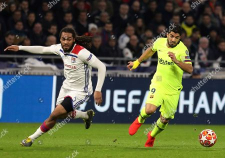 Lyon defender Jason Denayer, left, challenges Barcelona forward Luis Suarez, right, during the Champions League round of 16 first leg soccer match between Lyon and FC Barcelona in Decines, near Lyon, central France