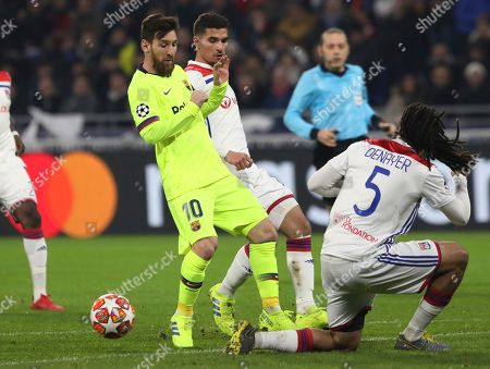 Lyon defender Jason Denayer, right, challenges Barcelona forward Lionel Messi, left, during the Champions League round of 16 first leg soccer match between Lyon and FC Barcelona in Decines, near Lyon, central France