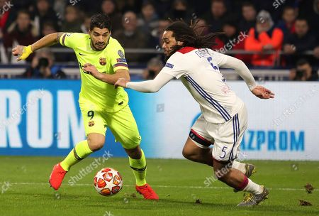 Barcelona forward Luis Suarez, left, challenges Lyon defender Jason Denayer, right, during the Champions League round of 16 first leg soccer match between Lyon and FC Barcelona in Decines, near Lyon, central France