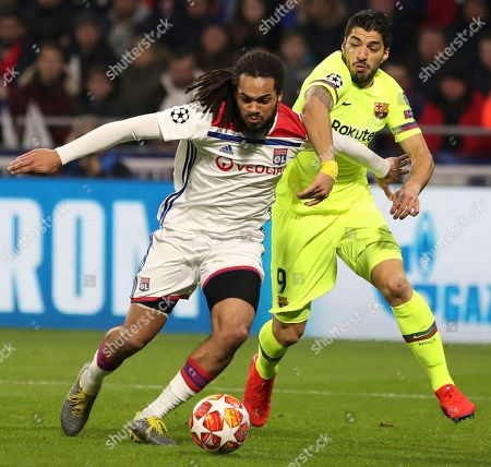 Barcelona forward Luis Suarez, right, challenges Lyon defender Jason Denayer, left, during the Champions League round of 16 first leg soccer match between Lyon and FC Barcelona in Decines, near Lyon, central France