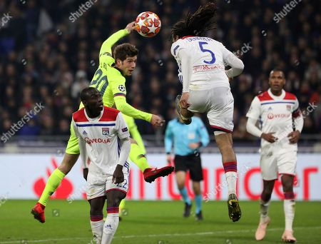 Barcelona midfielder Sergi Roberto, center, challenges Lyon defender Ferland Mendy, left, and Lyon defender Jason Denayer, right, during the Champions League round of 16 first leg soccer match between Lyon and FC Barcelona in Decines, near Lyon, central France