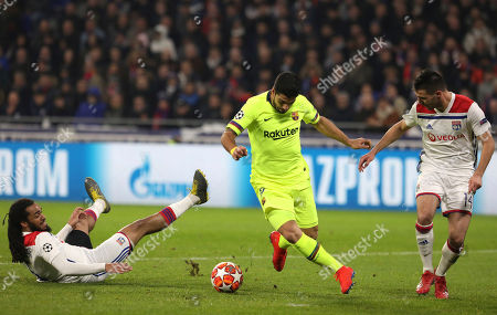 Lyon defender Jason Denayer, left, and Lyon defender Leo Dubois, right, challenge Barcelona forward Luis Suarez, center, during the Champions League round of 16 first leg soccer match between Lyon and FC Barcelona in Decines, near Lyon, central France