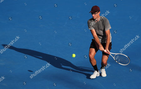 Stock Image of Peter Polansky, of Canada, returns the ball to John Isner, of the United States, during the first round of the Delray Beach Open ATP professional tennis tournament, played at the Delray Beach Stadium & Tennis Center in Delray Beach, Florida, USA