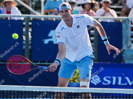 John Isner, of the United States, plays a volley against Peter Polansky, of Canada, during the first round of the Delray Beach Open ATP professional tennis tournament, played at the Delray Beach Stadium & Tennis Center in Delray Beach, Florida, USA