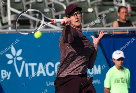 Stock Photo of Peter Polansky, of Canada, hits a forehand against John Isner, of the United States, during the first round of the Delray Beach Open ATP professional tennis tournament, played at the Delray Beach Stadium & Tennis Center in Delray Beach, Florida, USA