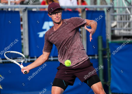 Peter Polansky, of Canada, hits a forehand against John Isner, of the United States, during the first round of the Delray Beach Open ATP professional tennis tournament, played at the Delray Beach Stadium & Tennis Center in Delray Beach, Florida, USA