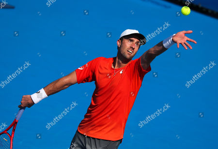 Steve Johnson, of the United States, lifts the ball to serve against Jason Jung, of Taipei, during the first round of the Delray Beach Open ATP professional tennis tournament, played at the Delray Beach Stadium & Tennis Center in Delray Beach, Florida, USA
