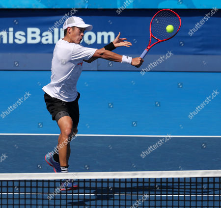 Stock Photo of Jason Jung, of Taipei, plays a volley against Steve Johnson, of the United States, during the first round of the Delray Beach Open ATP professional tennis tournament, played at the Delray Beach Stadium & Tennis Center in Delray Beach, Florida, USA
