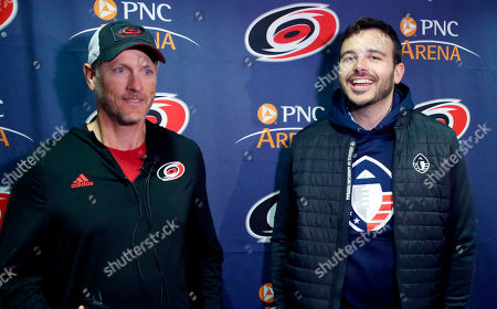 Tom Dundon, left, majority owner of the Carolina Hurricanes' and Charlie Ebersol, co-founder and CEO of the Alliance of American Football talk to the media about Dundon's $250 million investment in the league before the start of an NHL hockey game between the New York Rangers and the Carolina Hurricanes in Raleigh, N.C