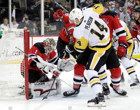 New Jersey Devils goaltender Keith Kinkaid (1) stops a shot s Pittsburgh Penguins left wing Tanner Pearson (14) attacks during the first period of an NHL hockey game, in Newark, N.J