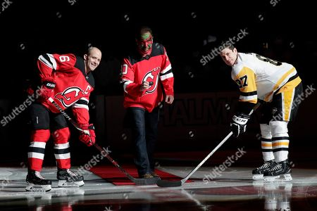 Actor Patrick Warburton, center, is dressed as Seinfeld cast member David Puddy, during a ceremonial puck drop with New Jersey Devils defenseman Andy Greene, left, and Pittsburgh Penguins center Sidney Crosby prior to an NHL hockey game, in Newark, N.J