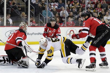 Pittsburgh Penguins left wing Jake Guentzel (59) falls to the ice while attacking against New Jersey Devils goaltender Keith Kinkaid (1), defenseman Andy Greene (6) and defenseman Ben Lovejoy (12) during the third period of an NHL hockey game, in Newark, N.J. The Penguins won 4-3