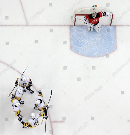 Pittsburgh Penguins players, bottom left, celebrate a goal by center Nick Bjugstad (27) as New Jersey Devils goaltender Keith Kinkaid (1) looks on during the first period of an NHL hockey game, in Newark, N.J. The Penguins won 4-3