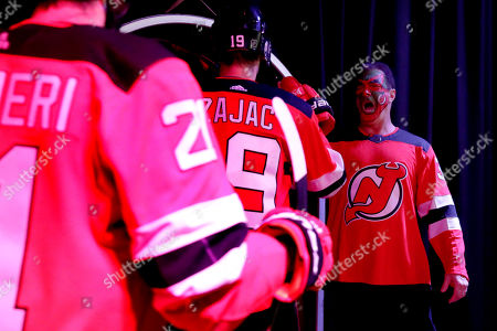 Actor Patrick Warburton, right, dressed as Seinfeld cast member David Puddy, greets New Jersey Devils players as they head to the ice for warmups prior to an NHL hockey game against the Pittsburgh Penguins, in Newark, N.J. The Penguins won 4-3