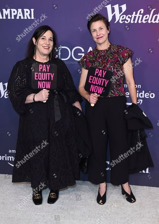 """Arianne Phillips, Nancy Steiner. Costume designers Arianne Phillips, left, and Nancy Steiner carry signs that read """"Pay Equity Now"""" as they arrive at the 21st annual Costume Designers Guild Awards at The Beverly Hilton Hotel, in Beverly Hills, Calif"""