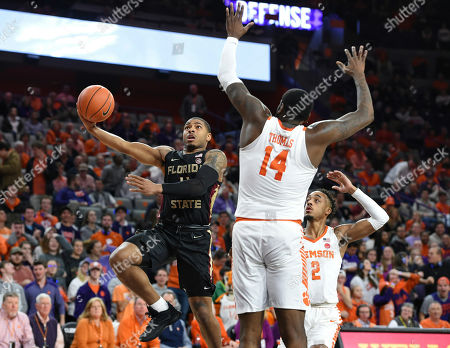 Florida State's David Nichols, left, drives to the basket while defended by Clemson's Elijah Thomas, right, during the first half of an NCAA college basketball game, in Clemson, S.C