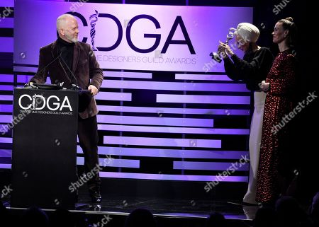 Ryan Murphy, Lou Eyrich, Sarah Paulson. Ryan Murphy, from left, accepts the distinguished collaborator award as Lou Eyrich bows and Sarah Paulson looks on at the 21st annual Costume Designers Guild Awards at The Beverly Hilton Hotel, in Beverly Hills, Calif