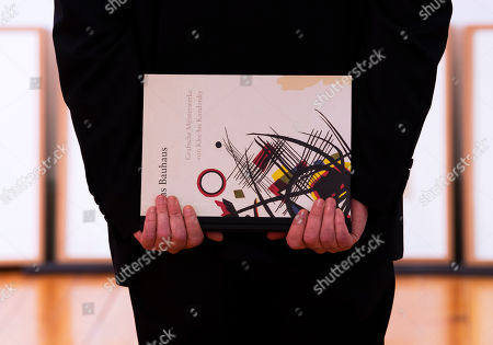 A man holds a catalog showing the lithograph 'Composition' (Komposition, 1922) by Wassily Kandinsky during the press preview of the exhibition 'Graphical masterpieces from Klee to Kandinsky' in the Lindenau Museum in Altenburg, Germany, . Germany is celebrating the 100th birthday of the Bauhaus art and design movement with different exhibitions this year. The exhibition starts on Feb. 24, 2019 and last until May 19, 2019