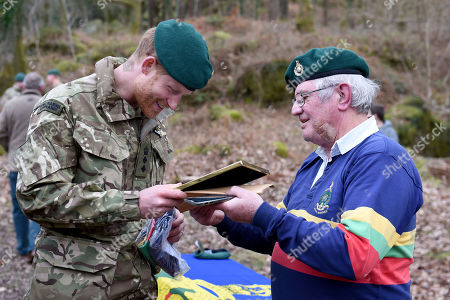 Prince Harry, Captain General Royal Marines, receiving a gift of a rugby shirt and a picture from former Marine Yorkie Malone, during his visit to 42 Commando Royal Marines at their base in Bickleigh to carry out a Green Beret presentation at Dartmoor National Park