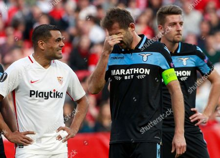 Sevilla's Gabriel Mercado, left, speaks with Lazio's Senad Lulic during the Europa League round of 32 second leg soccer match between Sevilla and Lazio at the Sanchez Pizjuan stadium, in Seville, Spain