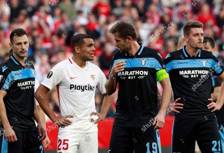 Sevilla's Gabriel Mercado, second left, speaks with Lazio's Senad Lulic during the Europa League round of 32 second leg soccer match between Sevilla and Lazio at the Sanchez Pizjuan stadium, in Seville, Spain