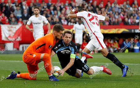 Sevilla's goalkeeper Tomas Vaclik (L) and defender Gabriel Mercado (R) in action against Lazio's midfielder Senad Lulic (C) during the UEFA Europe League round of 32 second leg match between Sevilla FC and SS Lazio at Ramon Sanchez Pizjuan stadium in Seville, Andalusia, Spain, 20 February 2019.