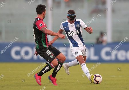 Enzo Dias of Argentina's Talleres, right, controls the ball under pressure from Luis Jimenez of Chile's Palestino during a Copa Libertadores soccer match in Cordoba, Argentina