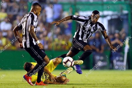 Marcelo Benvenuto, right, and Alex Santana of Brazil's Botafogo fight for the ball against Fernando Marquez of Argentina's Defensa y Justicia during a Copa Sudamericana soccer game in Florencio Varela, on the outskirts of Buenos Aires, Argentina